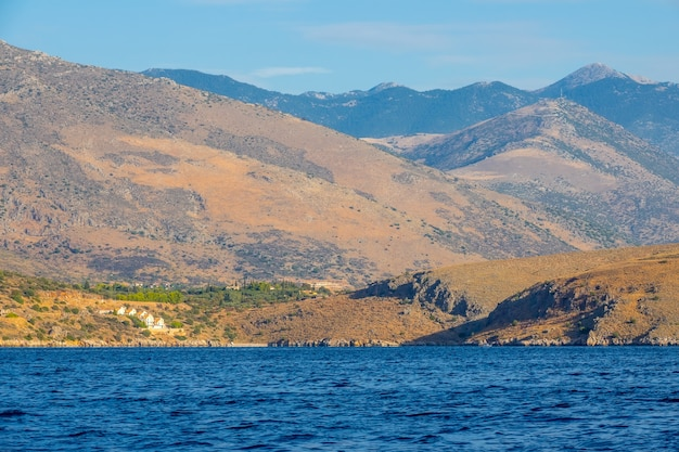 Greece. the hilly coast of the gulf of corinth. summer day. several cottages on the slope of a hilly coast