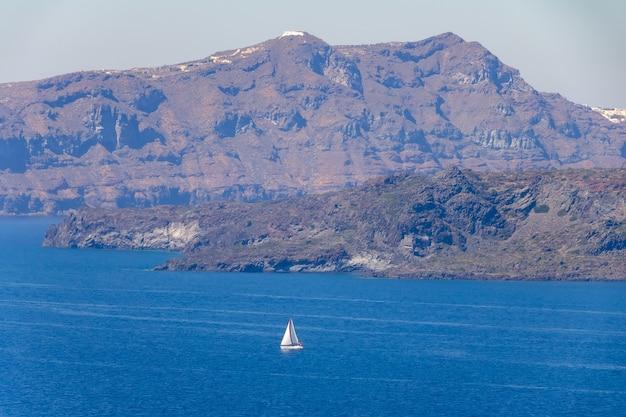 Греция. скалистый берег в солнечный день. белая парусная яхта. с высоты птичьего полета