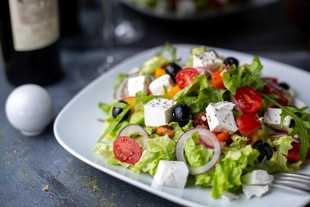 하얀 접시 안에 그리스 샐러드 슬라이스 올리브 레드 와인