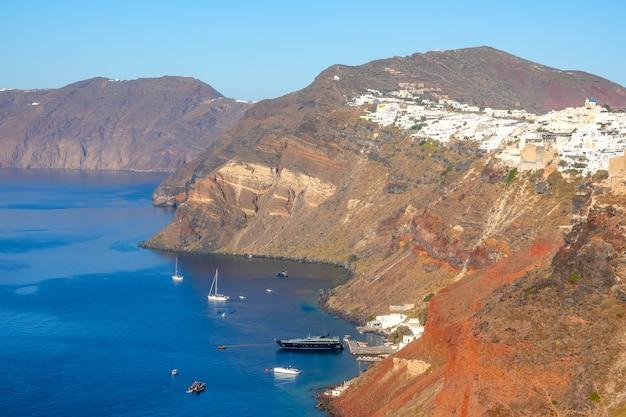 ギリシャ。晴れた日のサントリーニカルデラ。岩の多い海岸の斜面にあるイアの村。いくつかのセーリングとモーターヨット