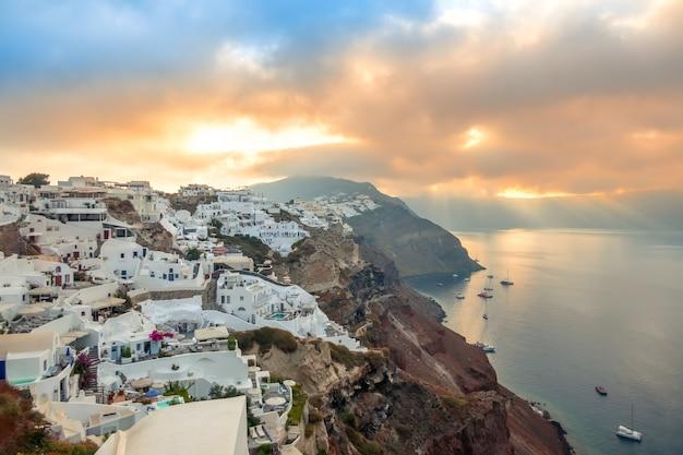 Греция. остров санторини. белые дома в ия на острове санторини. яхты и катамараны на якорной стоянке. рассвет