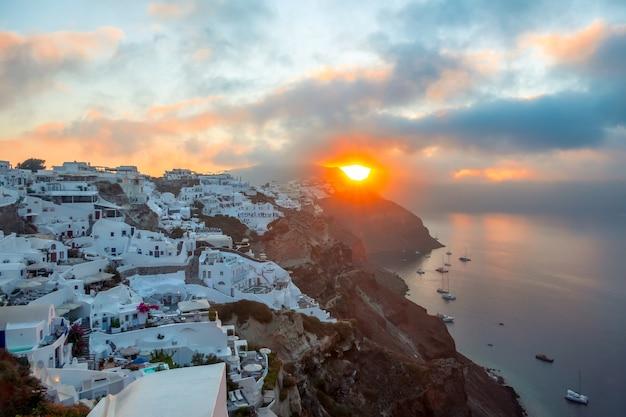 그리스. 산토리니 섬. 산토리니 섬 이아의 하얀 집. 정박지에 있는 요트와 쌍동선. 해돋이