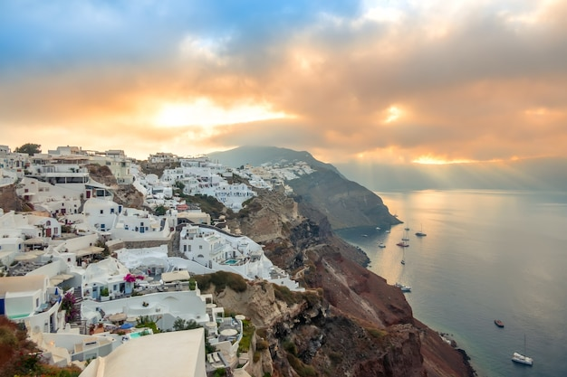 Greece. santorini island. white houses in oia on the island of santorini. yachts and catamarans in the anchorage. dawn