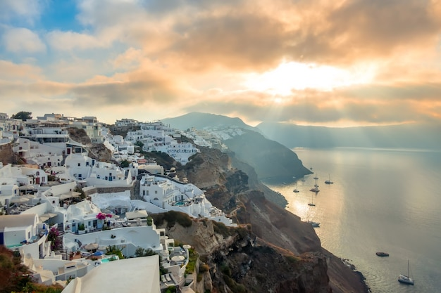 Греция. остров санторини. белые дома на острове санторини. яхты и катамараны на якорной стоянке. восход