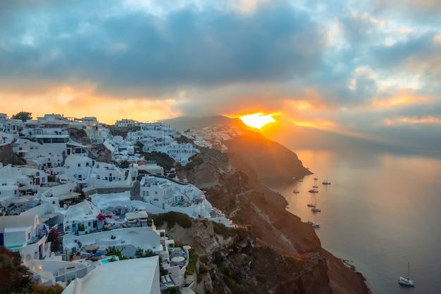 그리스. 산토리니 섬. 산토리니 섬의 하얀 집. 요트와 쌍동선. 해돋이