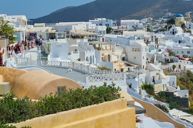 그리스, 산토리니, 이아. 산토리니의 유명한 그리스 섬, 인기있는 관광 마을 이아. 전통적인 흰색 건축, 바다, 산, 하늘 및 많은 관광객이 걷고 휴식하는 사람들