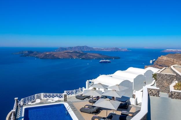 그리스. 산토리니. 티라 섬. 이아의 높은 은행에있는 호텔. 화창한 날씨에 휴식을 취할 수있는 수영장과 일광욕 용 라운 저. 바다 경치