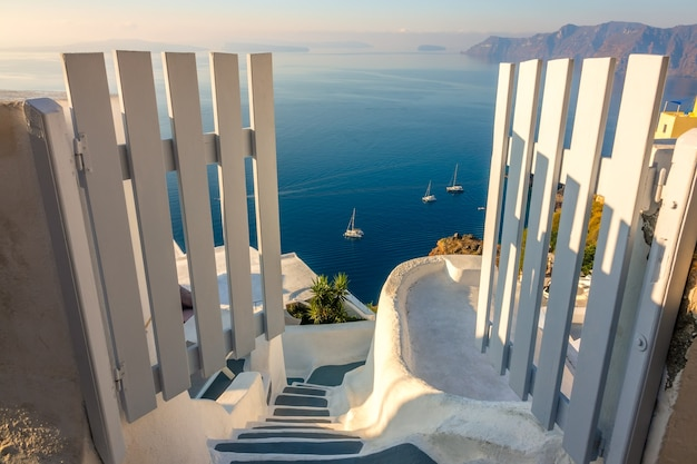 Greece. santorini. thira island. open gate and steps down. seascape from the height of the caldera