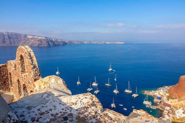 ギリシャ。サントリーニ。ティラ島。イアの遺跡と港の帆走カタマランの上面図