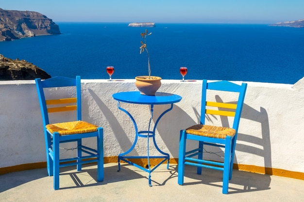 ギリシャ。サントリーニ。ティラ島。イアのカフェからの日当たりの良い海の景色。椅子2脚とグラス2杯のワイン