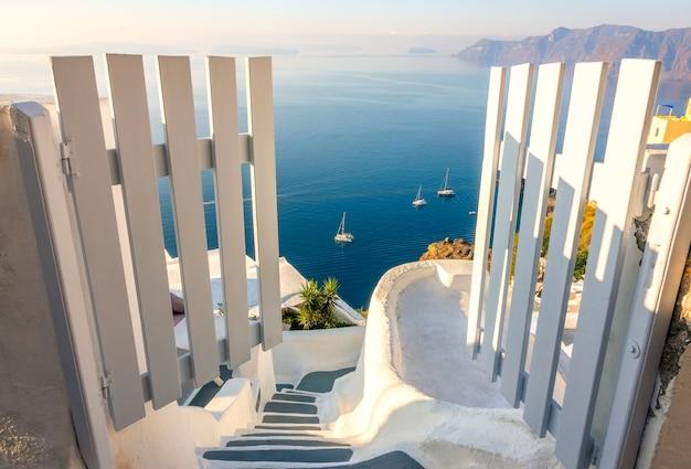 그리스. 산토리니. 티라 섬. 화이트 게이트와 계단. 칼데라 높이에서 바라본 바다 경치와 요트
