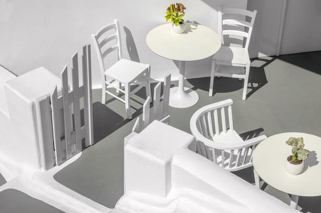 Греция. санторини. остров тира. белый стол и стулья на солнечной террасе