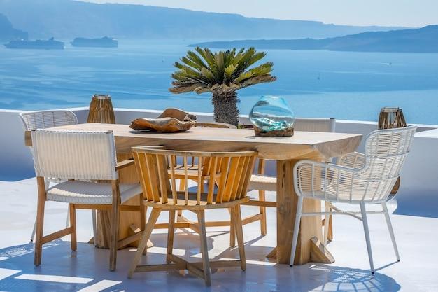 그리스. 산토리니. 티라 섬. 나무 테이블과 의자는 일광욕 테라스에 있습니다. 항구에서 두 개의 유람선