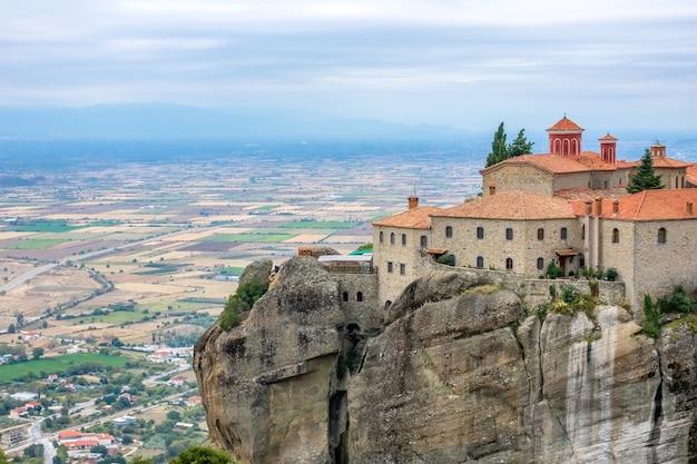 ギリシャ。メテオラの夏の日。町と野原の上の高い崖の上の修道院