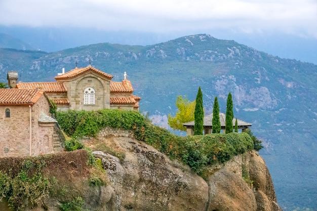 Греция. летний вечер в каламбаке. беседка на вершине холма и скальный монастырь с видом на горные вершины