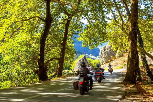 Greece. summer sunny day in the forest shade on a mountain road. group of motorcycle tourists