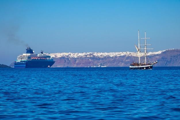 Греция. солнечный день у берегов санторини. старый трехмачтовый корабль и многопалубный круизный лайнер