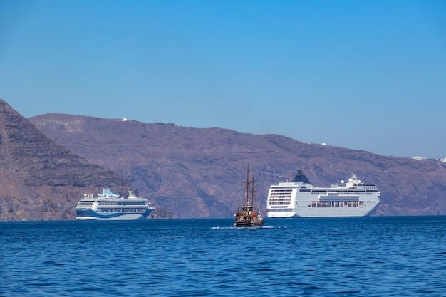 Греция. солнечный день у берегов санторини. два круизных многопалубных корабля и старый трехмачтовый корабль