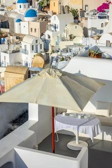 그리스. 산토리니 섬의 칼데라에서 화창한 날. 야외 테라스의 파라솔 아래 테이블 제공