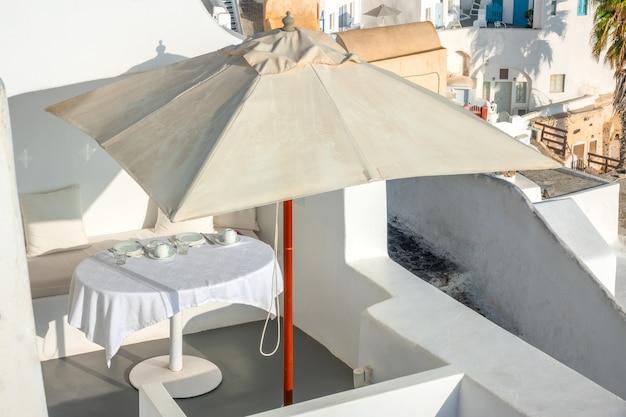 그리스. 산토리니 섬의 칼데라에서 화창한 여름날. 오픈 테라스의 우산 아래 식탁보가 있는 테이블 제공