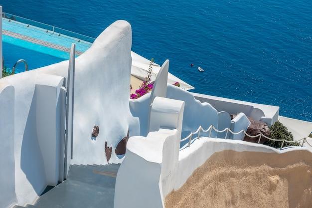 그리스. 산토리니 섬의 칼데라에서 화창한 여름날. 바다에 전통적인 계단입니다. 흰 벽, 푸른 수영장 가장자리와 꽃 덤불