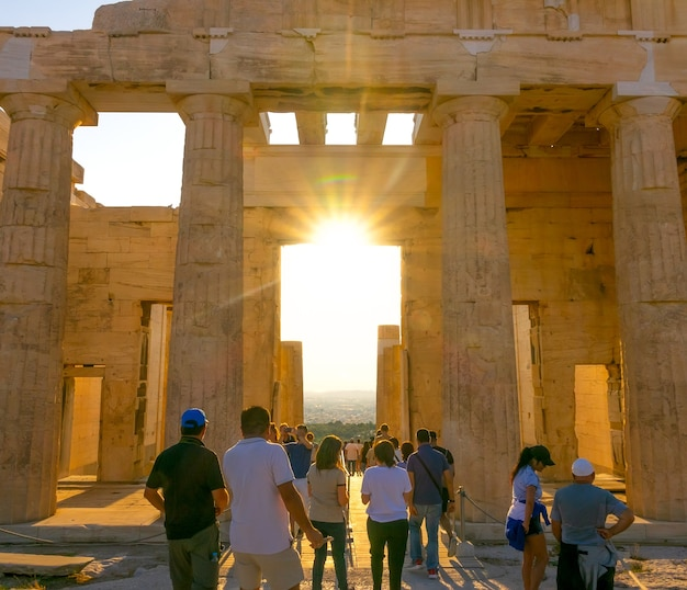 ギリシャ。夏のアテネに沈む夕日。パルテノン神殿への入り口の柱廊玄関の観光客