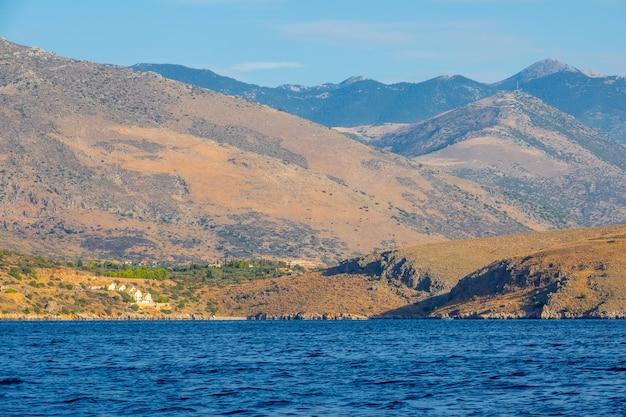 그리스. 고린도만의 언덕이 많은 해안. 여름날. 언덕이 많은 해안의 경사면에있는 여러 오두막