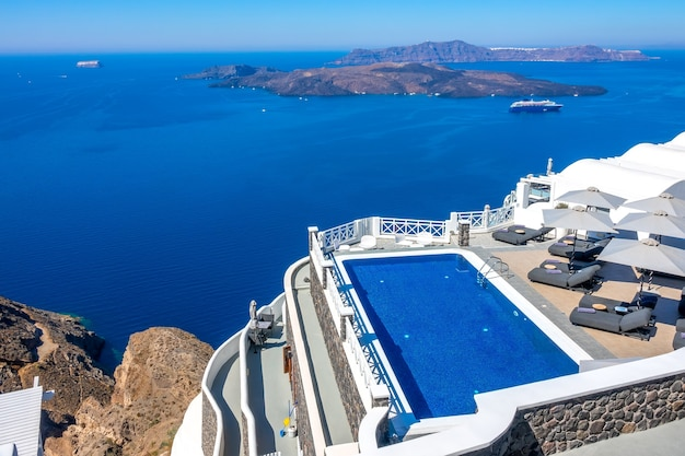 그리스. 티라 섬. 산토리니. 이아의 높은 은행에있는 호텔. 화창한 날씨에 휴식을 취할 수있는 수영장과 일광욕 용 라운 저. 바다 경치
