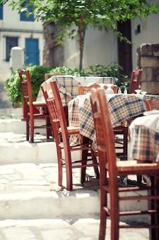 Таблицы и стулья кафа снаружи, афины, greece.toned винтажное фото.