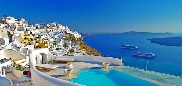 Путешествие по греции. замечательный отдых на острове санторини. роскошный курорт с бассейном и видом на вулкан.