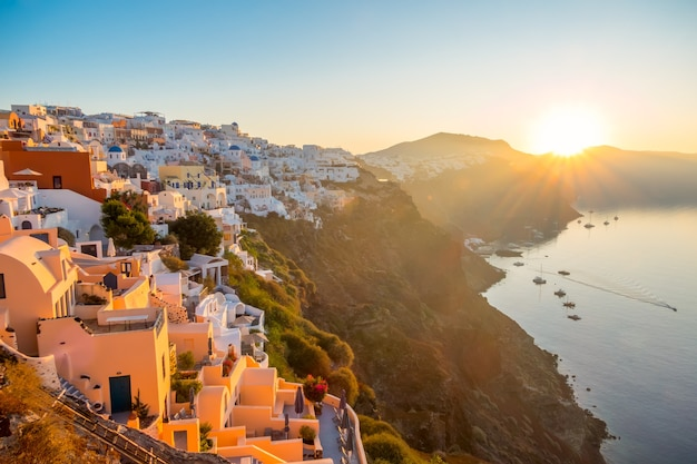 Greece. volcanic island of thira (santorini). cloudless dawn over the caldera. many white houses of oia city on the side of a mountain and a yacht in the harbor