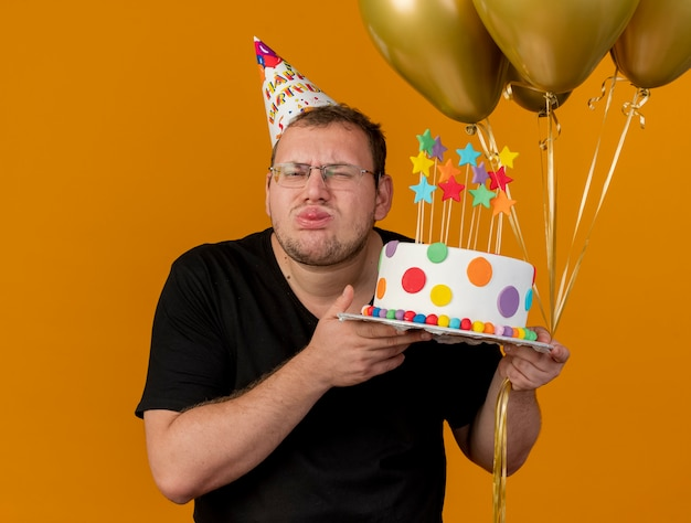 Greedy adult slavic man in optical glasses wearing birthday cap stucks out tongue holds helium balloons and birthday cake
