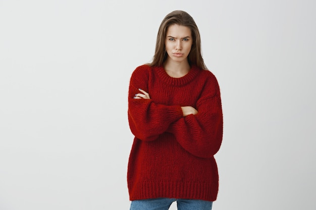 Greedy attractive girlfriend feeling displeased and jealous. portrait of offended european woman in red loose sweater, frowning and sulking, being annoyed and angry, standing with crossed hands