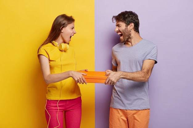 Greedy female and male cannot share box, both hold orange package, shout at each other, have annoyed expressions, wear vivid colorful clothes, stand against two colored background.