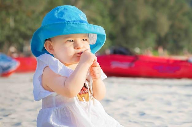 Жадная девушка что-то ест на пляже и не хочет делиться она в белом платье синяя шляпа