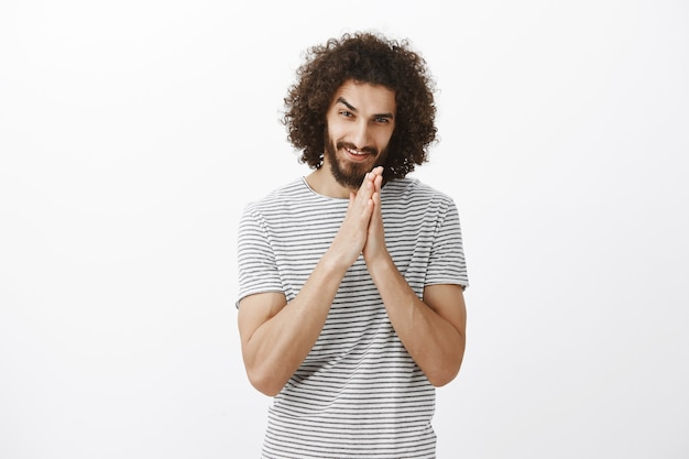 Greedy guy has nasty plan. portrait of intrigued curly-haired man with beard, rubbing palms together near chest and smiling