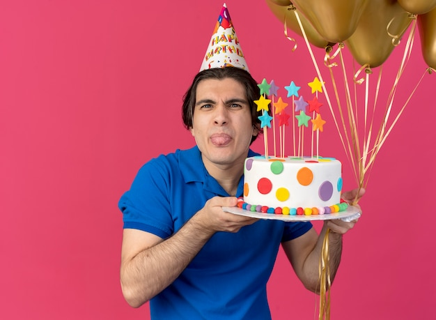 Greedy handsome caucasian man wearing birthday cap stucks out tongue holds helium balloons and birthday cake