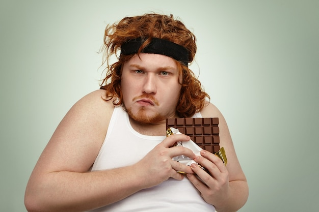 Greedy obese fat young man wearing sports band on curly ginger hair