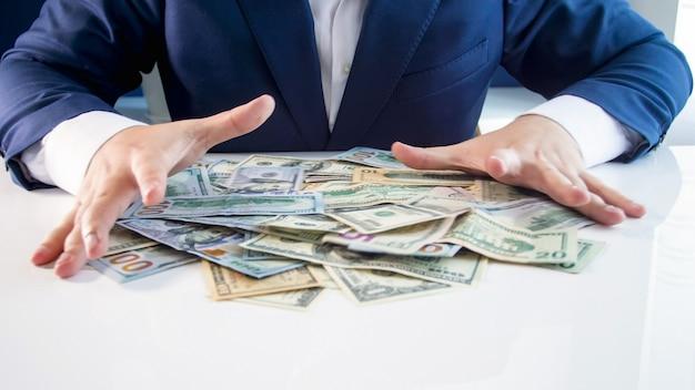 彼の机からお金の山をつかむ貪欲な金持ちの実業家。金融投資、経済成長、銀行貯蓄の概念。