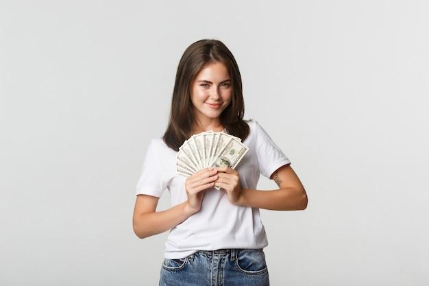 狡猾に見え、お金を持って、白く立っている貪欲な笑顔の女の子。