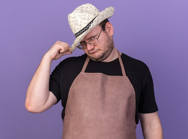 파란색 벽에 고립 된 원예 모자를 쓰고 낮춘 머리 젊은 남성 정원사와 욕심
