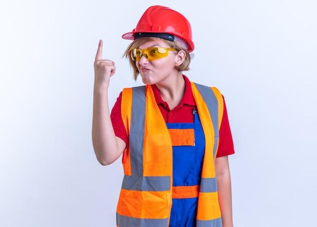 白い背景で隔離の1つを示す眼鏡と制服を着た貪欲な若いビルダーの女性