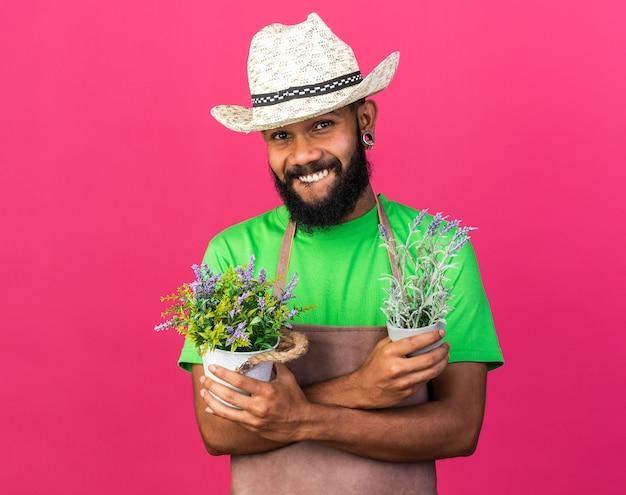 Avido giovane giardiniere afro-americano che indossa un cappello da giardinaggio tenendo e attraversando fiori in vaso di fiori isolato su parete rosa