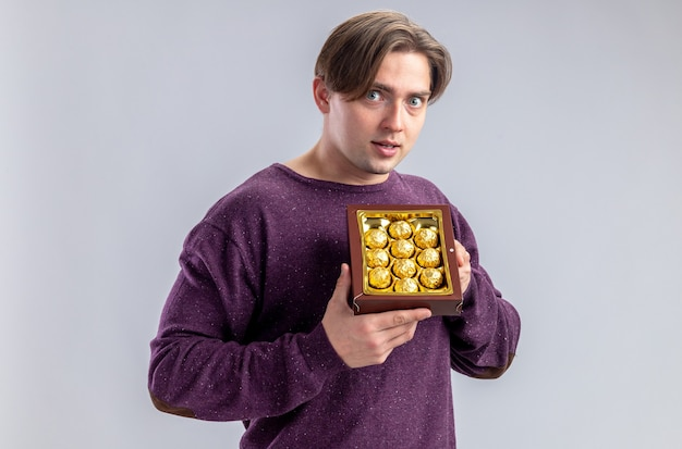 Greedy young guy on valentines day holding box of candies isolated on white background