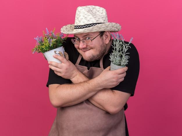 ピンクの壁に隔離された植木鉢に花を持ち、花を交差させるガーデニング帽子をかぶった貪欲な若い男性の庭師