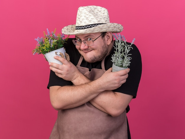 Greedy young male gardener wearing gardening hat holding and crossing flowers in flowerpots isolated on pink wall