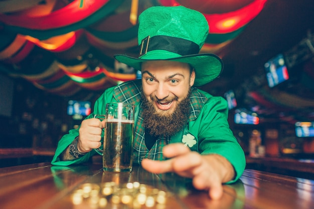 Greedy young man in green st. patrick's suit reaching golden coins. he it at table in pub and hold mug of beer.