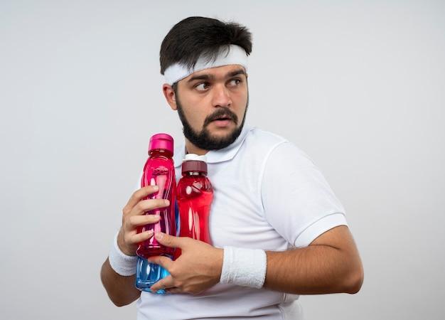 Avido giovane sportivo che indossa la fascia e il braccialetto che tengono le bottiglie d'acqua isolate sul muro bianco