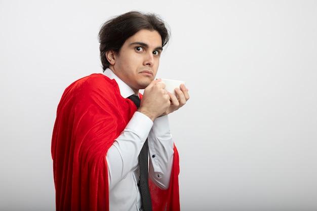 白で隔離のお茶のカップを保持しているネクタイを身に着けているカメラを見て貪欲な若いスーパーヒーローの男