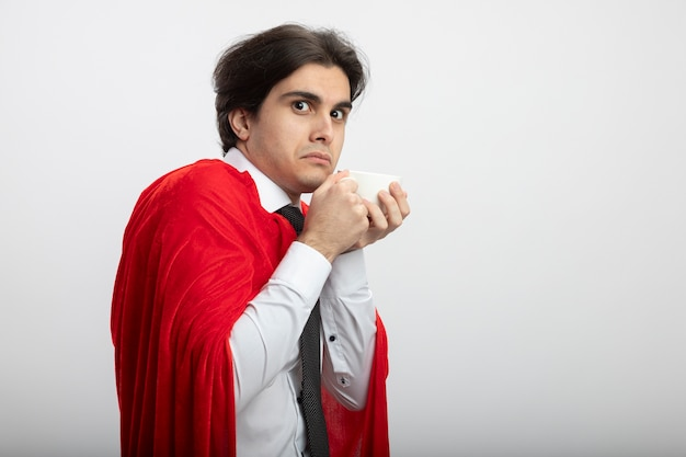 Greedy young superhero guy looking at camera wearing tie holding cup of tea isolated on white